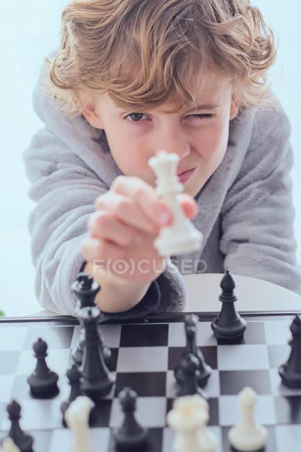 Boy showing chess figure near chess board — Stock Photo