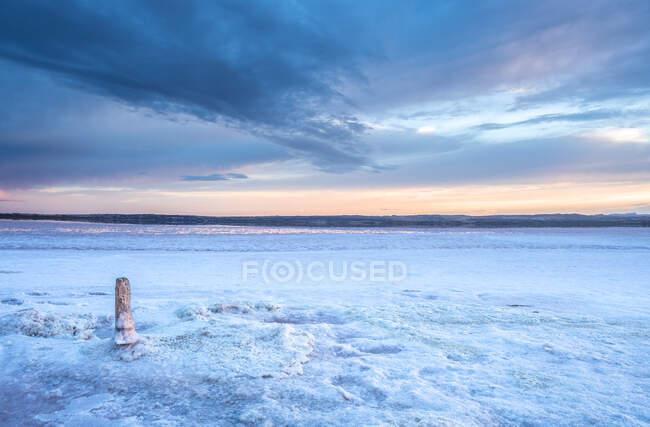 Stick on salt mine during sunset — Stock Photo