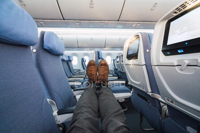 Legs of anonymous man in stylish pants and shoes lying on comfortable seats inside modern aircraft — Stock Photo