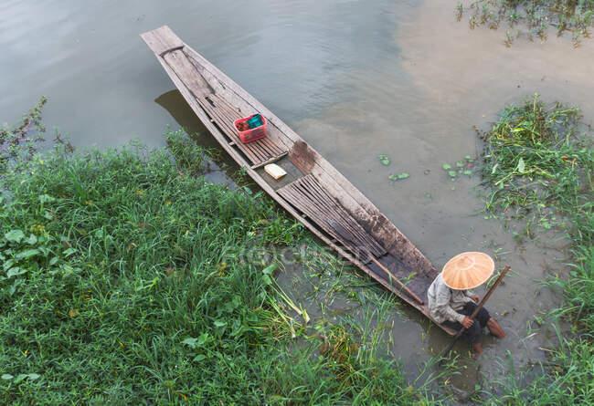 Shan, Myanmar - 25 de junho de 2012: De cima homem irreconhecível sentado em barco de madeira perto da costa verde, enquanto a pesca em Inle Lake — Fotografia de Stock