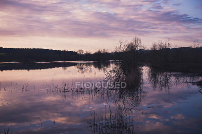 Cloudy evening sky over calm lake in countryside — Stock Photo