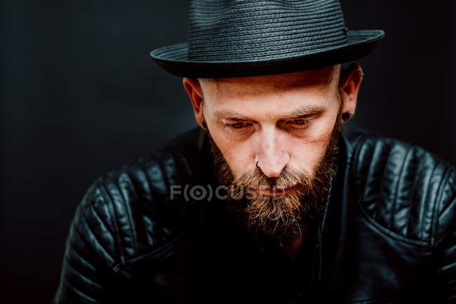 Cool hipster in hat and leather jacket looking down on black background — Stock Photo