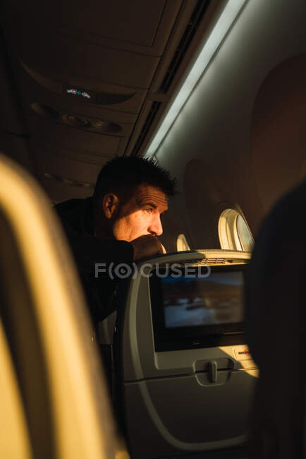 Thoughtful man looking out plane window — Stock Photo