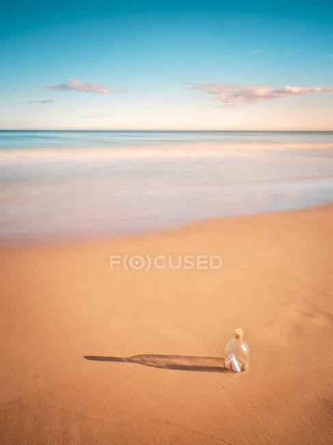 Bottle in sand near sea — Stock Photo