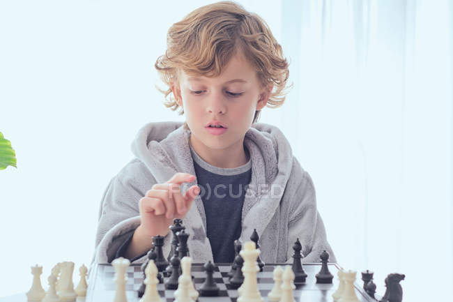 Boy holding figure on chess board — Stock Photo