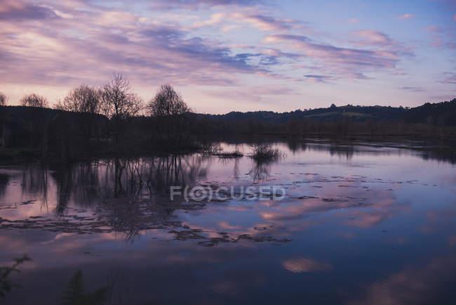 Ciel nuageux en soirée sur un lac calme à la campagne — Photo de stock