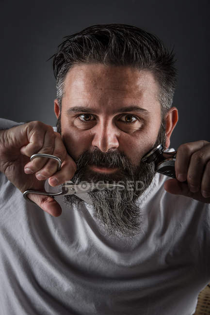Expressive barber cutting beard — Stock Photo