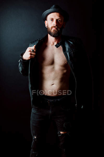 Shirtless cool hipster in hat adjusting leather jacket and looking at camera on black background — Stock Photo