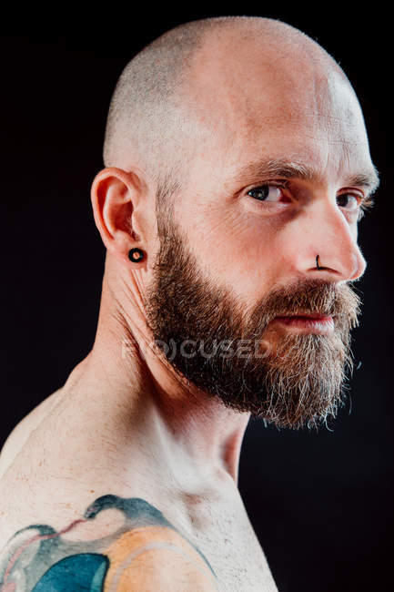 Вид сбоку лысого хипстера с серьгой и блестками на черном фоне — стоковое фото