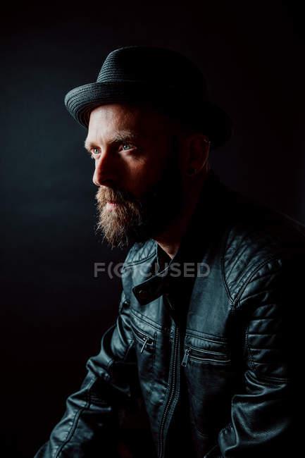 Cool hipster en chapeau et veste en cuir regardant loin sur fond noir — Photo de stock