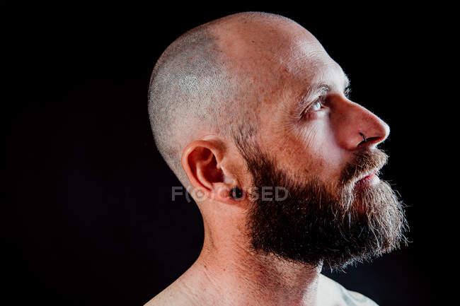 Vista lateral de calvo hipster reflexivo con pendiente y piercing mirando hacia otro lado sobre fondo negro - foto de stock