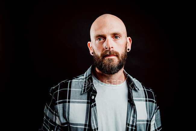 Bearded hairless hipster in shirt looking at camera on black background — Stock Photo