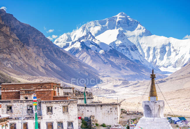 Majestic view of grungy old houses and traditional temple against fantastic snowy mountain peak on sunny day in Tibet — Stock Photo