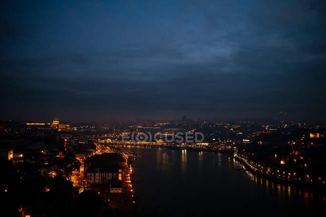 Bella vista drone di cielo scuro nuvoloso su magnifica città illuminata e fiume calmo di notte — Foto stock