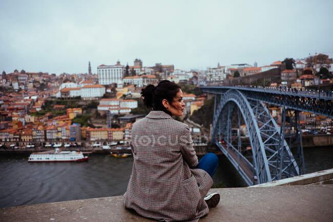 Vista posteriore di bella femmina in abito alla moda guardando altrove mentre seduto vicino al ponte moderno in maestosa città invecchiata — Foto stock