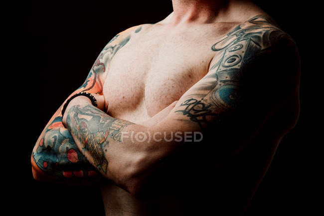Side view of crop shirtless hipster with crossed hands and tattoos on hands on black background — Stock Photo