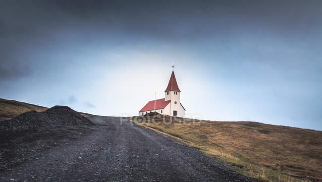 Precioso edificio de la iglesia situado cerca de camino campo áspero contra el cielo nublado en Islandia - foto de stock