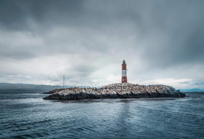 Sinal na pequena ilha rochosa no mar tempestuoso em dia nublado — Fotografia de Stock