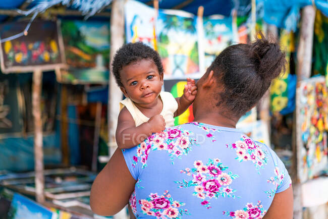 Back view of African American mother holding little kid near small souvenir shop in Jamaica — стокове фото