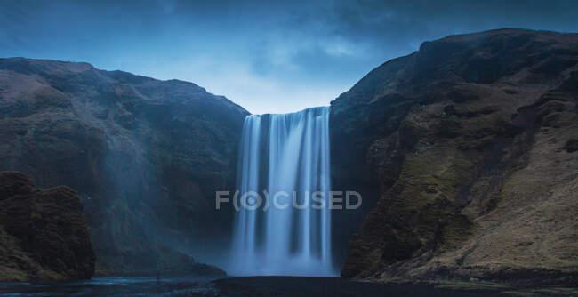 Vista mozzafiato di una magnifica cascata e ruvida scogliera in una bella giornata nuvolosa in Islanda — Foto stock
