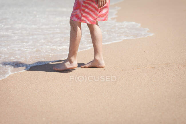 Legs of anonymous barefoot person in striped shorts standing on sandy beach near foamy waving sea water on sunny day — Stock Photo