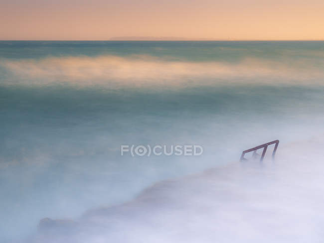 Wonderful foggy sea waving near rough stony shore — Stock Photo