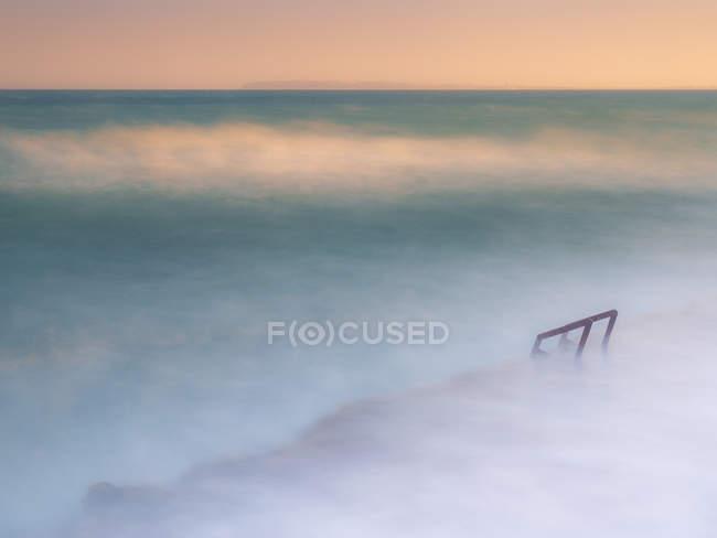 Merveilleuse mer brumeuse agitant près du rivage pierreux rugueux — Photo de stock