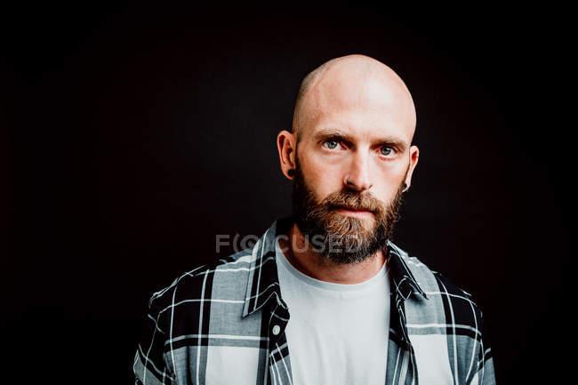 Hipster sin cabello en camisa mirando a la cámara sobre fondo negro. - foto de stock