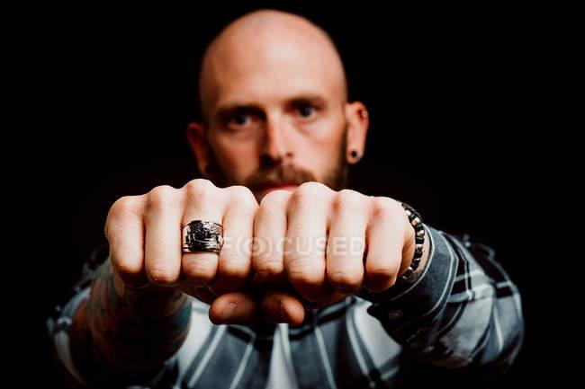 Hipster serio barbuto in camicia con tatuaggi a portata di mano che mostra pugni con anello su sfondo nero — Foto stock