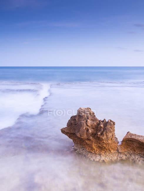 Дивовижні камені на березі біля води і блакитного неба. — стокове фото