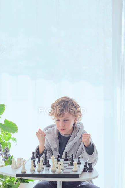 Menino segurando figura no tabuleiro de xadrez — Fotografia de Stock