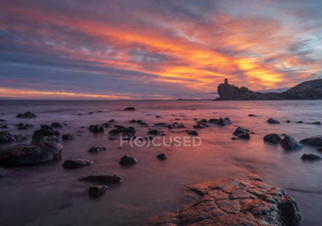 Яскраві хмарно вечірнє небо над величний моря і скелястий берег — стокове фото