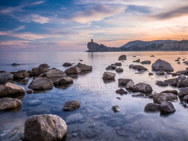 Beautiful view of bright cloudy evening sky over majestic sea and rocky shore in spectacular nature — Stock Photo