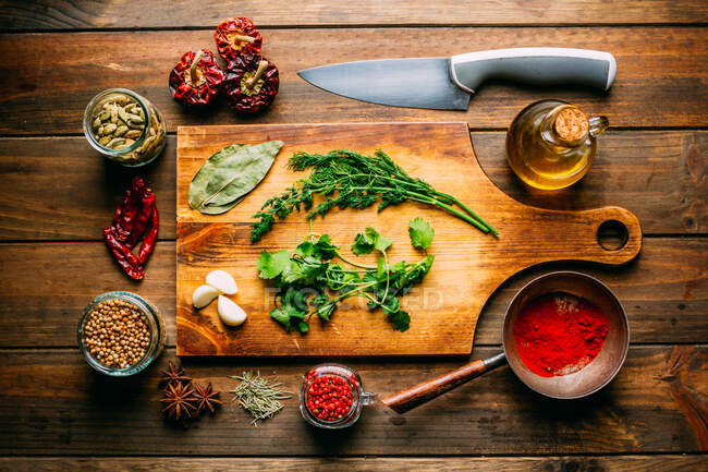 From above various spices and bottle of oil placed on timber tabletop near sharp knife — Stock Photo