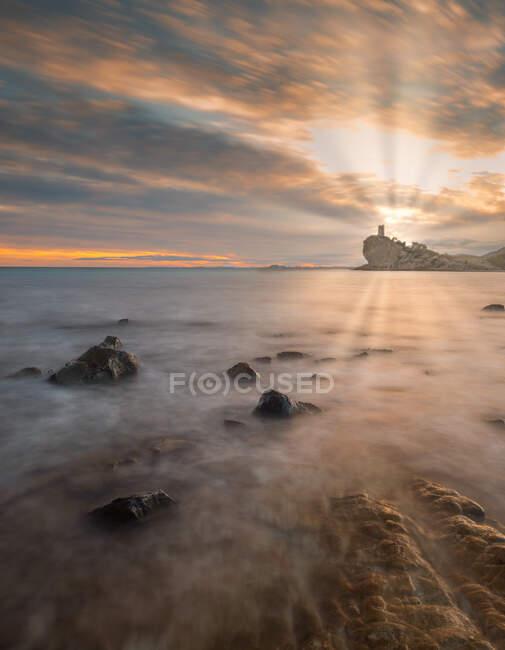 Belle vue sur un ciel nocturne nuageux et lumineux sur la mer majestueuse et le rivage rocheux dans une nature spectaculaire — Photo de stock