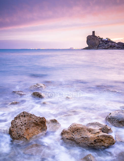 Bright cloudy evening sky over majestic sea and rocky shore — Stock Photo