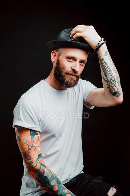 Веселий бородатий гіпстер у капелюсі та футболці з татуюваннями на руках на чорному тлі. — стокове фото