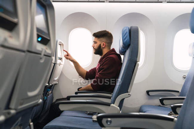 Side view of bearded guy browsing aircraft gadget while sitting on comfortable seat inside modern plane — Stock Photo