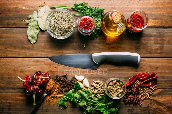 D'en haut diverses épices et bouteille d'huile placée sur une table en bois près d'un couteau tranchant — Photo de stock
