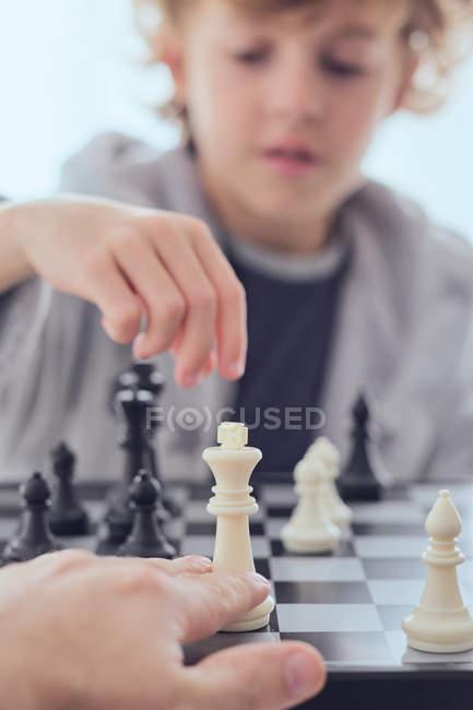 Мальчик держит фигуру на шахматной доске — стоковое фото
