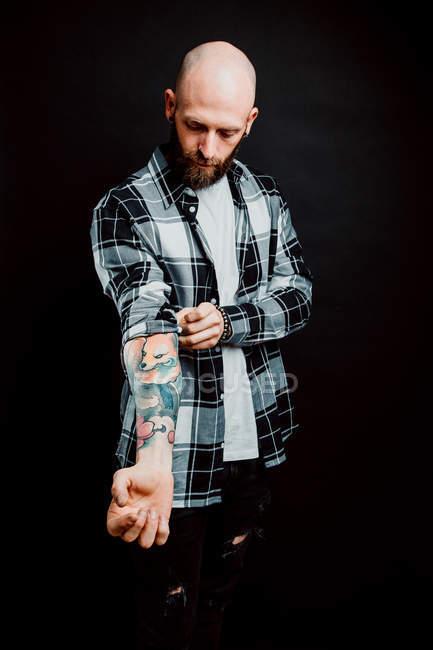 Бородатый хипстер в рубашке с татуировками на руках на черном фоне — стоковое фото