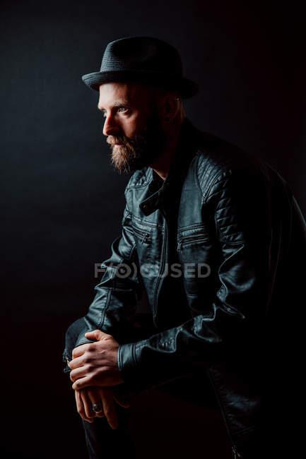 Hipster frais en chapeau et veste de cuir sur fond noir — Photo de stock