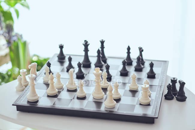 From above chess board with white and black figures on table on blurred background — Stock Photo