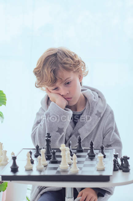 Boy holding figure on chess board — Stock Photo