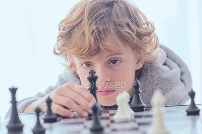 Хлопець, що тримає фігуру на шахівниці — стокове фото