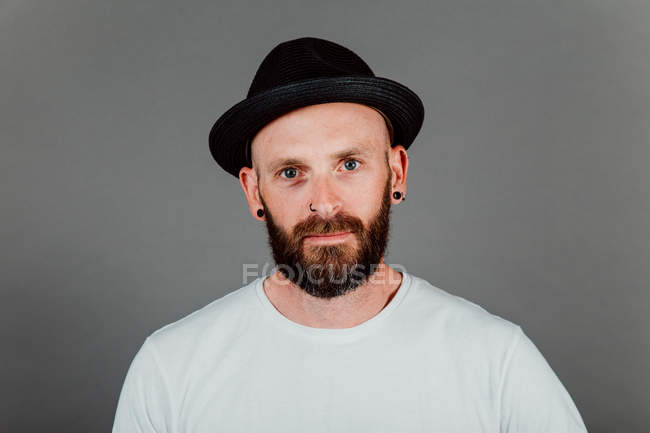 Bearded hairless hipster in t-shirt and hat on black background — стокове фото