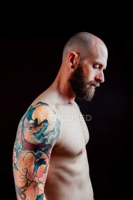 Vista laterale di hipster serio calvo senza maglietta con tatuaggi sulle braccia che distolgono lo sguardo su sfondo nero — Foto stock