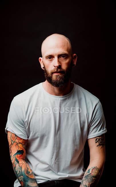 Bärtiger, haarloser Hipster im T-Shirt mit Tätowierungen an den Armen auf schwarzem Hintergrund — Stockfoto