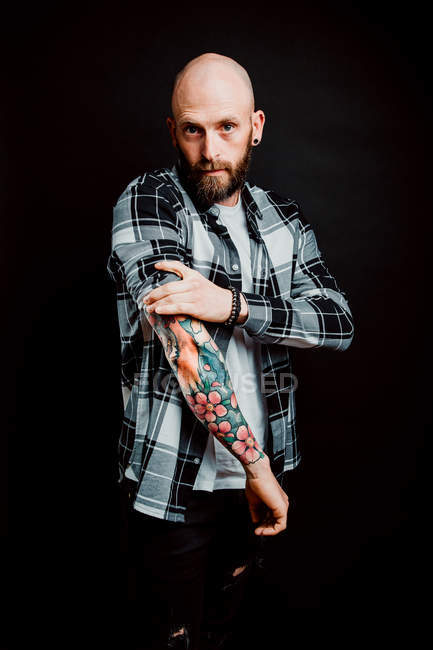 Bearded hairless hipster in shirt with tattoos on arms on black background — Stock Photo