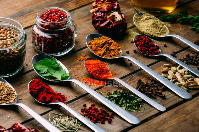 Bunch of assorted spices placed in order on lumber tabletop near bottle of oil — Stock Photo